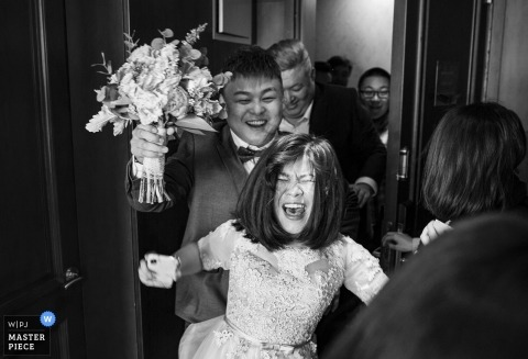 Beijing documentary wedding photo of very excited bride entering room with bouquet
