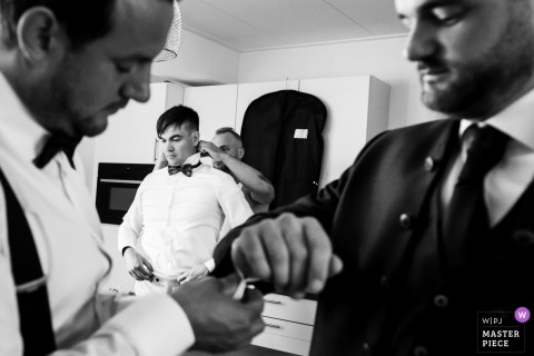 NL Wedding photojournalism at Noord Brabant - groom getting dressed with friends