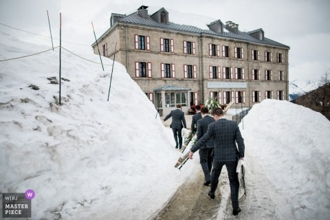 French wedding photograph of groomsmen arriving in the snow in Chamonix