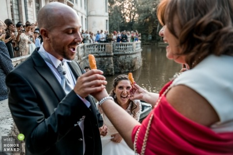 Documentary wedding photography of groom about to eat at Château d'Ermenonville - France
