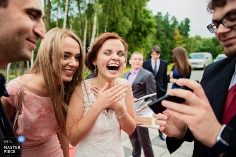 Wedding photojournalism of bride with great expression with guests at Gdańsk