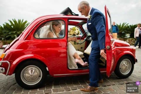 Brescia wedding shoot with a bride and father arriving in small car - The bride arrives