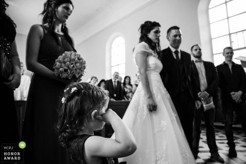 Hochzeitsfotojournalismusbild der Vogesen eines Paares während der Zeremonie und ein Flowergirl mit den Fingern in ihren Ohren