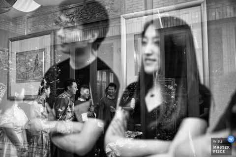 Wedding pictures by Beijing photographer - Friends can be seen reflected in glass as they watch the wedding