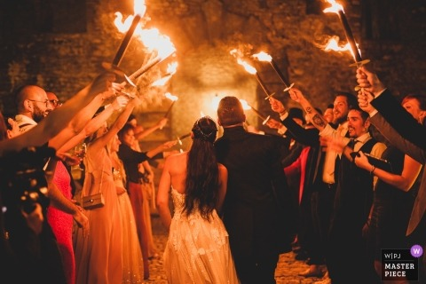 Rome wedding shoot with a couple leaving their reception party under a gauntlet of guests with flaming torches