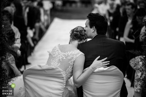 De bruidegom van Oost-Vlaanderen kust bruid op het hoofd tijdens hun huwelijk