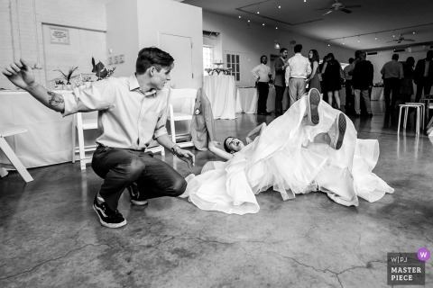 Wedding photojournalism at Chicago reception hall with bride laying on her back after falling down