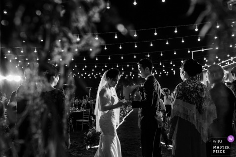 Ha Noi wedding photojournalism black and white image of a couple exchanging rings during lit ceremony