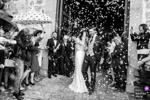 Madrid wedding shoot with a couple exiting church with confettii and umbrellas