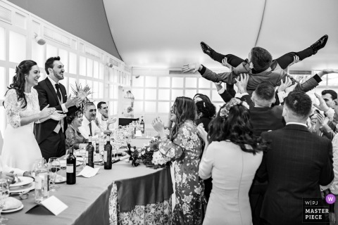 Wedding photo shoot at a Madrid reception with guests in the air before bride and groom