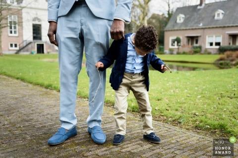 Hochzeits-Fotojournalismus in Zuid Holland von Groomsmen und kleinem Jungen in passenden Outfits beim Hochzeitsempfang