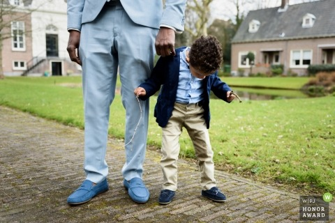 Wedding photojournalism at Zuid Holland of groomsmen and small boy in matching outfits at the wedding reception