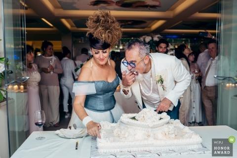 Zdjęcia ślubne Massy i Carrary z parą tnącą ciasto na weselu