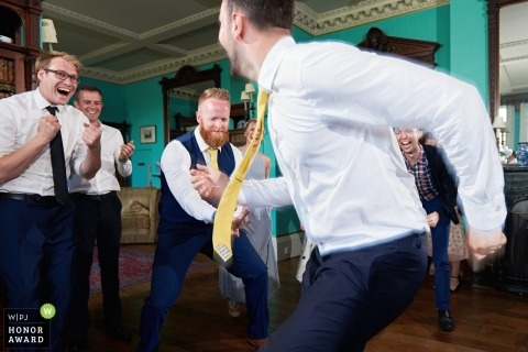 Wedding photojournalism of groomsmen dancing at Prestwold Hall, Leicestershire, UK