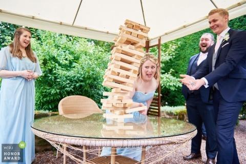 Dokumentarische Hochzeitsphotographie des hölzernen Blockturmes Jenga, der bei Goldstone Hall, Markt Drayton, Shropshire fällt