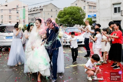 Hangzhou City wedding photojournalism image of a couple getting sprayed with silly string