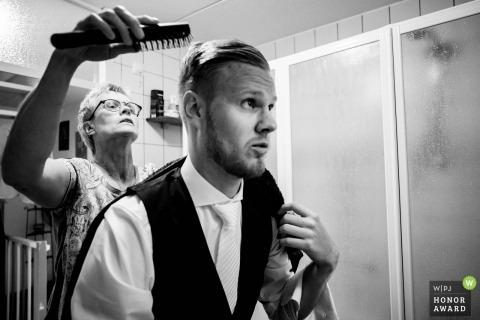 uden dokumentarisches Hochzeitsfoto des Bräutigams, der Hilfe mit seinem Haar beim Fertigmachen erhält