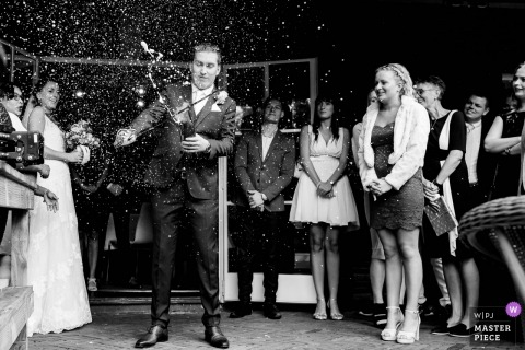 tilburg wedding photo shoot of groom cutting off bottle top at reception