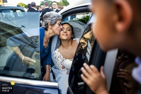 Documentary wedding photography of a bride getting a kiss from relative inside limo | weddings in Reggio Calabria