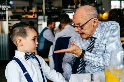 The Case Restaurant, Leicester | Dziadek za pomocą gestów rąk, aby porozmawiać z chłopakiem ze strony, który wydaje się trzymać swój w rozmowie