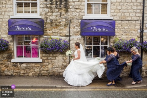 image of a London bride walking on wet streets with help from bridesmaids keeping her dress clean and dry