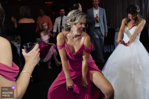 Bruidsmeisje en Bruid die bij de de Ontvangstpartij van het Huwelijk van Atlanta dansen