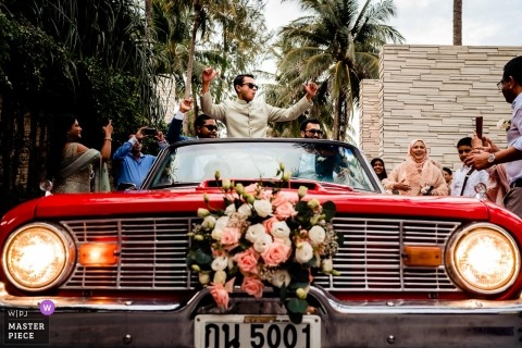 Phuket wedding photograph of groom arriving in vintage convertible auto in Thailand