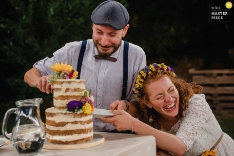 Sofia couple during their wedding Bulgaria reception party as the laugh during the cake cutting