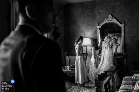 Wedding photojournalism of a bride preparing in a mirror in Tuscany