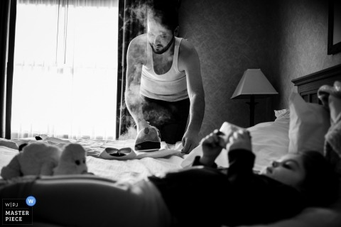 Documentary wedding photography of groom ironing and steaming his shirt in Omaha, NE