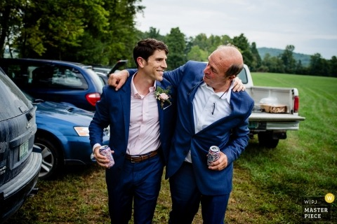 image of a Burlington, Vermont groom walking and talking with a friend at his outdoor wedding
