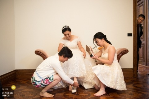 Victoria - AU documentary wedding photo of a bride getting help putting on her shoes