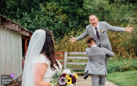 Nebraska Wedding Photograph of groom being carried away from his bride.