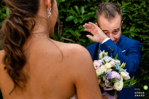 Antwerpen wedding photojournalism | image of a couple with the groom wiping tears as he holds brides bouquet