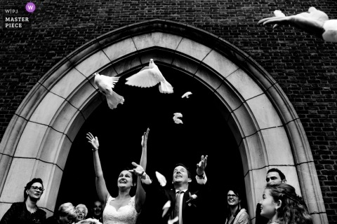 Pictures of a couple releasing doves after church ceremony by a top Antwerpen wedding photographer
