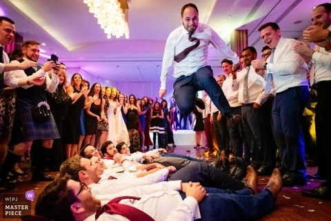 Wedding photojournalism image of guest jumping over guys at a London, UK reception