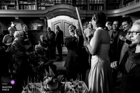 Wedding photo shoot in Tiel-Holland of cake cutting couple with huge sword
