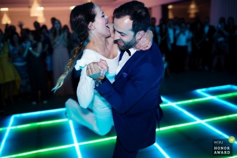 Paredes, Portugal  wedding photojournalism image of a couple during their first dance with neon dance floor lighting