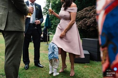 Roman Camp Hotel, Callander wedding reception photo of a toddler hiding under moms dress.