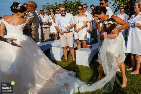 Havana, Cuba documentary wedding photo of flower girl getting caught up in bride's veil during the outdoor ceremony