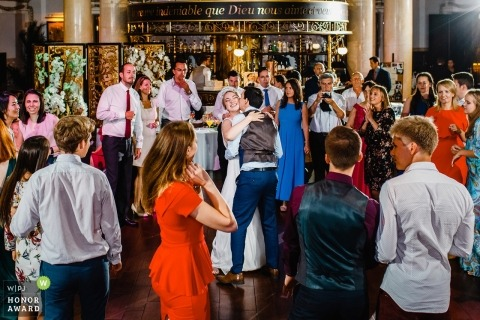 Saint-Petersburg wedding shoot with a couple dancing on crowded dance floor with guests