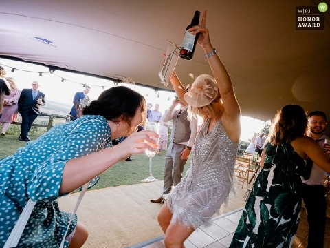 Wedding pictures of guests having drinks on the dancefloor by Napton Windmill, Napton photographer