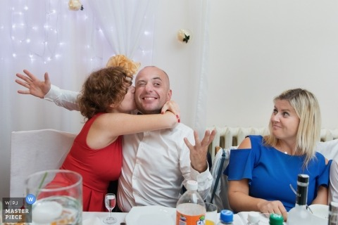 Krakow guests kissing during a wedding reception party