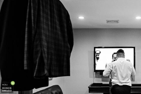 Foto de boda documental de Nueva Jersey | El padre de la novia ayuda a su hijo con una corbata con espectador de televisión en el fondo en la boda de Rock Island Lake Club NJ