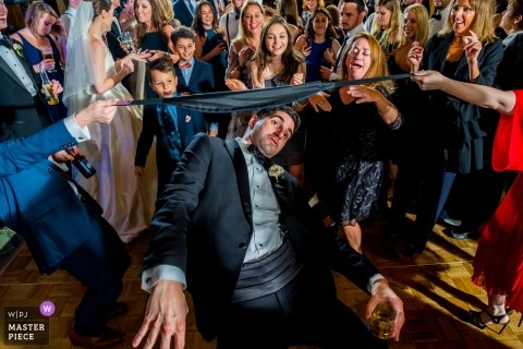 Bloomfield Hills Country Club, Michigan | Man getting low under the limbo during reception party