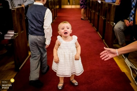 Eleva, Wisconsin wedding ceremony photograph of young girl crying in aisle by a Madison, WI wedding photographer