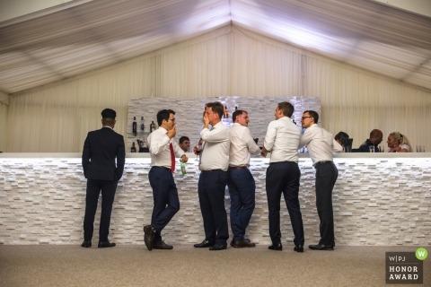 Ditton Manor, London, UK Hochzeitsfotografie von Jungs an der Bar während des Empfangs