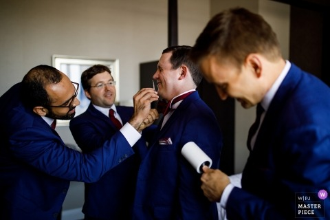 Groomsmen helping the groom get ready at the Ravisloe Country Club