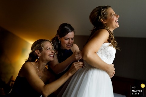 Pictures of a bride getting helped into her dress - Grand Rapids wedding photographer