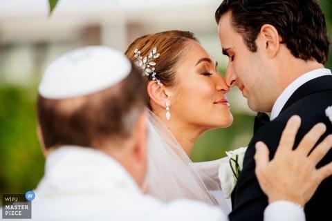 Riviera Maya Huwelijksfotografie van bruid en bruidegom van aangezicht tot aangezicht tijdens openluchtceremonie.